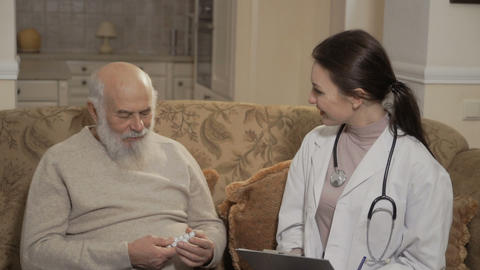Doctor prescribe pills to senior man Footage