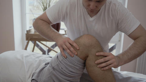 Doctor massages kne and leg of old patient Footage
