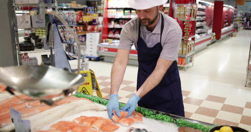 Fishmonger in store arranging fish counter Footage