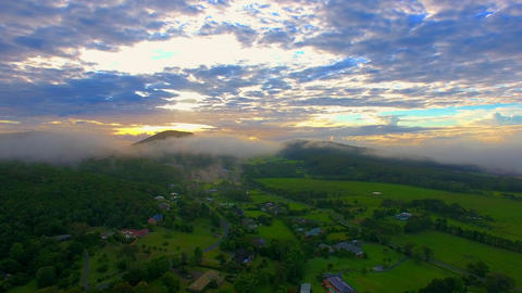 Foggy sunrise behind a mountain with lush landscape Footage