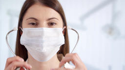 Portrait of professional female doctor in mask standing in hospital room. Woman Footage