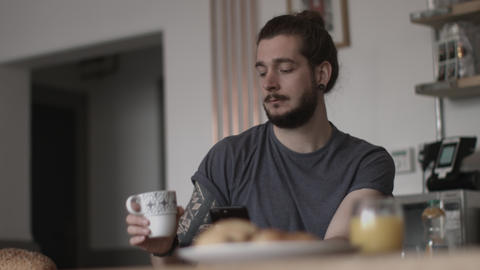 Young adult male having morning coffee and checking smartphone GIF