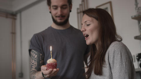 Boyfriend giving girlfriend a birthday cupcake Live Action