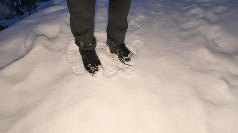 Man legs in dark trousers and high outdoor boots walking in snow while heavy Image