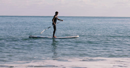 Female practice paddle boarding in the sea ビデオ