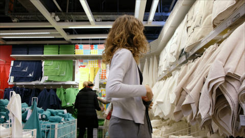 A young girl chooses the towels in the supermarket, 4K Live Action