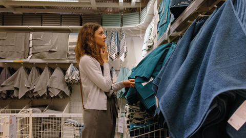 A young woman chooses the towels in the shopping center, 4K Footage