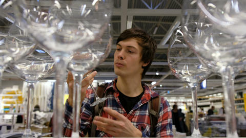 A young man chooses the glasses in the supermarket, 4K Live Action