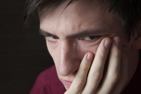 A close-up portrait of a guy a sad heavy look a fist propping his cheek Photo