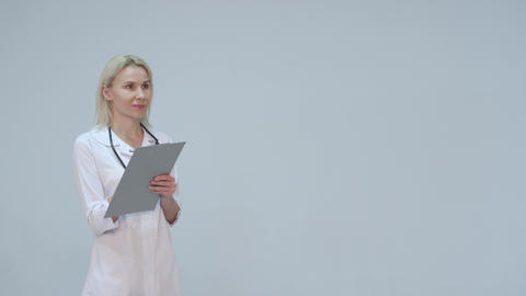 Young female doctor in white room writing Footage