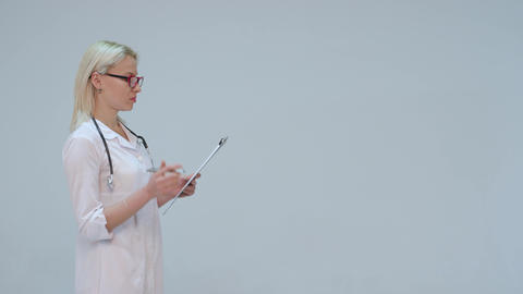 Blonde Doctor writing on a clipboard while smiling against a grey background Footage
