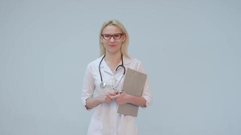 Portrait of a female doctor with white coat and stethoscope smiling looking into Footage