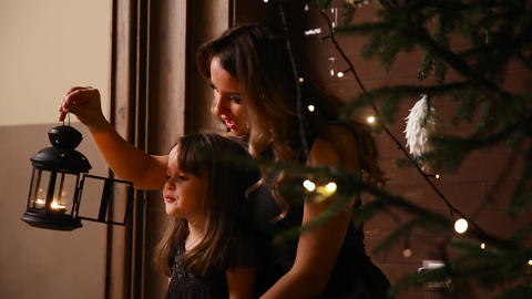 Mom and her daughter sit under a Christmas tree blow out a torchlight with a Footage