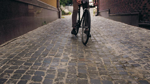 4k footage of stylish man riding black vintage bicycle om paved road of narrow Footage