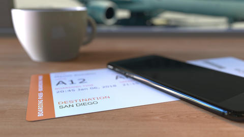 Boarding pass to San Diego and smartphone on the table in airport. Travelling to Footage