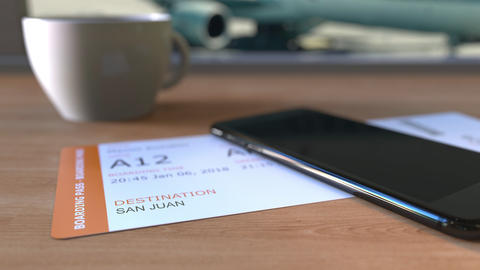Boarding pass to San Juan and smartphone on the table in airport. Travelling to Footage