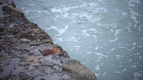 The sea breakwater is washed by waves in slow motion Footage