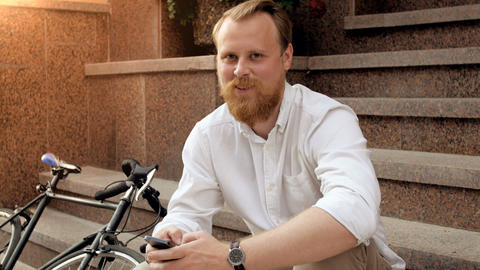 4k portrait of happy smiling red bearded hipster man sitting on staircase Footage