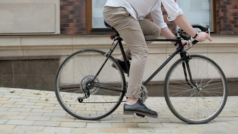 Slow motion video of stylish hipster man riding vintage bicycle out of narrow Footage