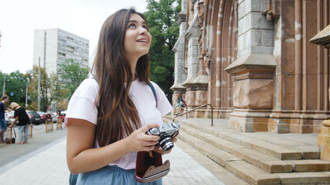 4k footage of smiling brunette girl making photographs on retro film camera Footage