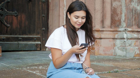 Slow motion footage of beautiful girl with long hair sitting on street and Footage