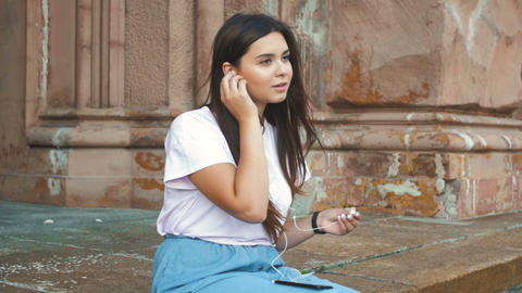 Slow motion video of smiling young woman sitting on street and listening music Footage