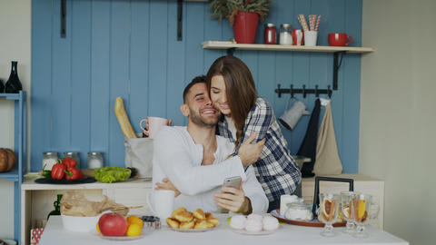 Attractive couple meet in the kitchen at breakfast time and using smartphone for Photo