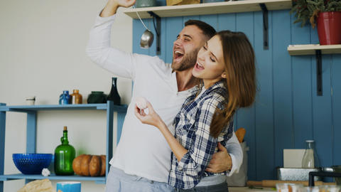 Joyful couple have fun dancing and singing in the kitchen at home in the morning Photo