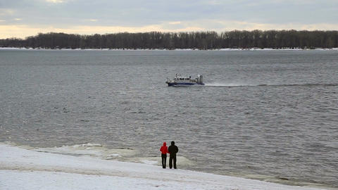 A man and a woman standing on the shore watching floating hovercraft Footage