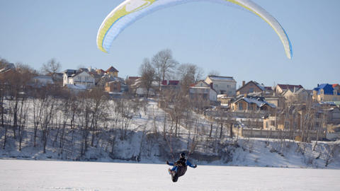 Pilot of the paraglider landed on a frozen lake Image