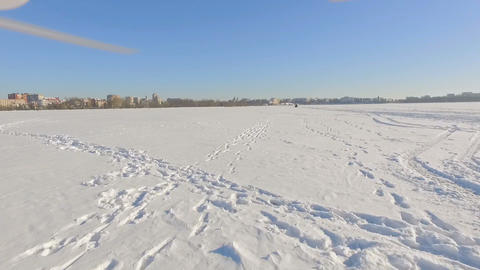 drone flies over a frozen lake near a city park in the background of a winter ビデオ