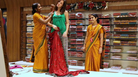 Indian Shop Assistant Puts on Red Sari to Woman Footage