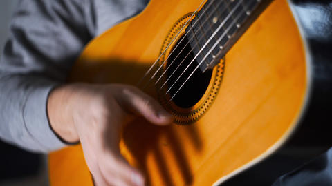 Guitar player plays scales and gamms on the acoustic western guitar with steel Filmmaterial