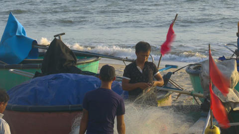 Asian Fishermen Check Net at Round Boats with Red Flags Footage