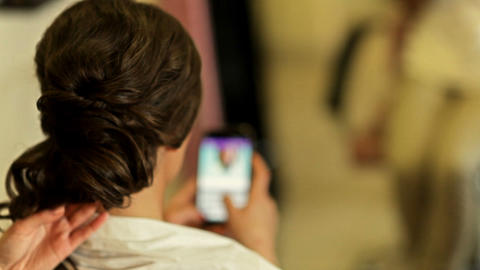 The girl does a hairdress at the hairdresser and looks through her iPhone Live Action