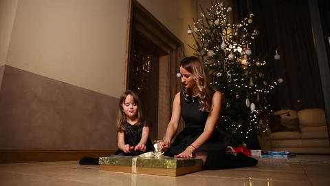Mom and daughter sitting under the Christmas tree open gifts. The girl untying Footage