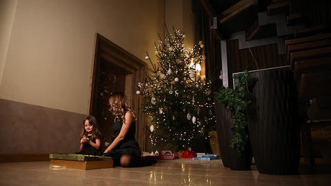 Mom and daughter sitting under the Christmas tree open gifts. Overall plan Footage