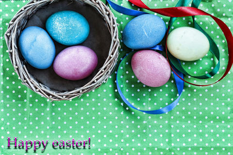 Easter. Easter eggs in a basket on a green background and colored ribbons. Happy Foto