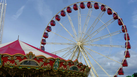 Red ferris wheel spins with red carousel Footage