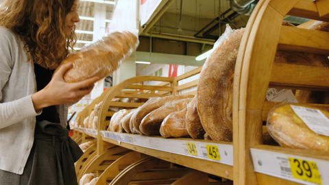 Girl sniffing fresh bread in a store, 4k Live Action