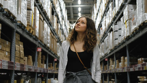 Young girl looking for your goods in the warehouse of the supermarket, 4k Live Action
