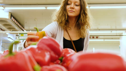 Beautiful caucasian girl chooses a red pepper in a vegetable shop, 4k Footage