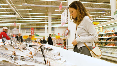 Girl chooses a fish in a fish department in a supermarket, 4k Live Action