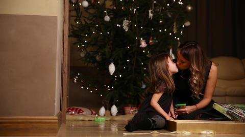Mom and daughter sitting under the Christmas tree open gifts. A girl untying a Footage