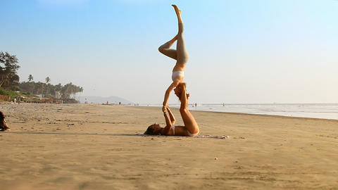 Girls Perform Stunning Yoga Pose on Wet Sea Beach Live Action