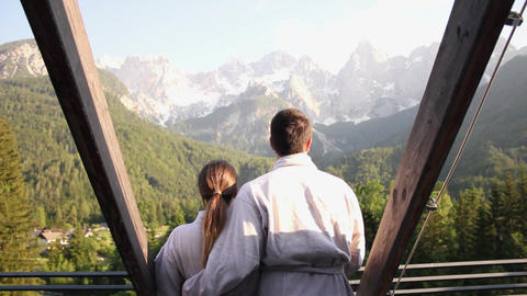 Couple embraced in spa looking at mountain panorama Footage