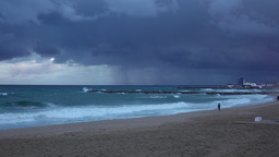 Surfer run along empty beach, severe weather, leaden sky, rainy clouds Live Action