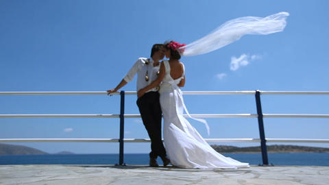 Beautiful bride and groom on the beach. Veil brides beautifully fluttering in ビデオ