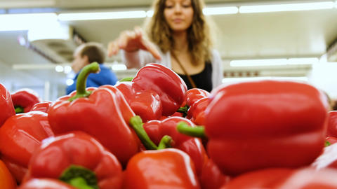 Beautiful girl chooses red pepper in a supermarket, in the blur, 4k Footage