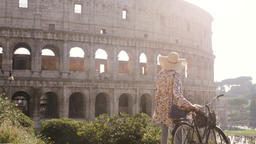 Beautiful young woman in colorful fashion dress alone on hill with bike looking Footage